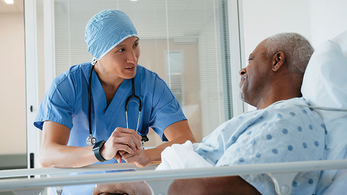 A doctor in scrubs chats with a smiling patient in a hospital bed.