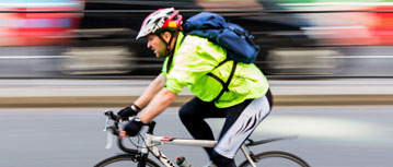 Male bike commuter zooms to work in brightly colored clothes and helmet