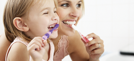 photograph of a mother and daughter brushing teeth