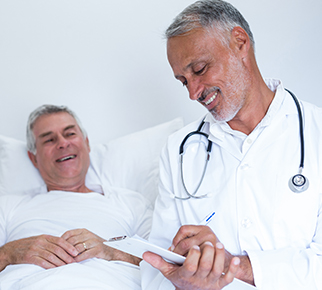 A doctor smiling while reading charts, and a patient happily laying in bed