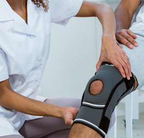 Image: Occupational medicine - placing a knee brace on a man's leg