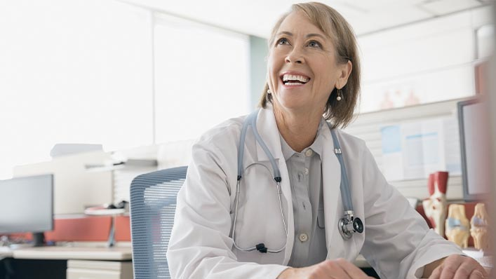 Clinician looks up from desk, smiling